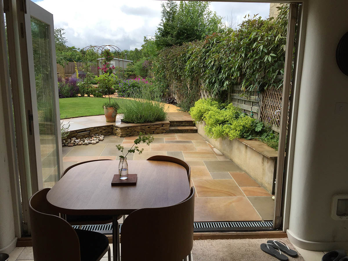 View from the kitchen of the natural stone paving, entertaining area and safe water feature