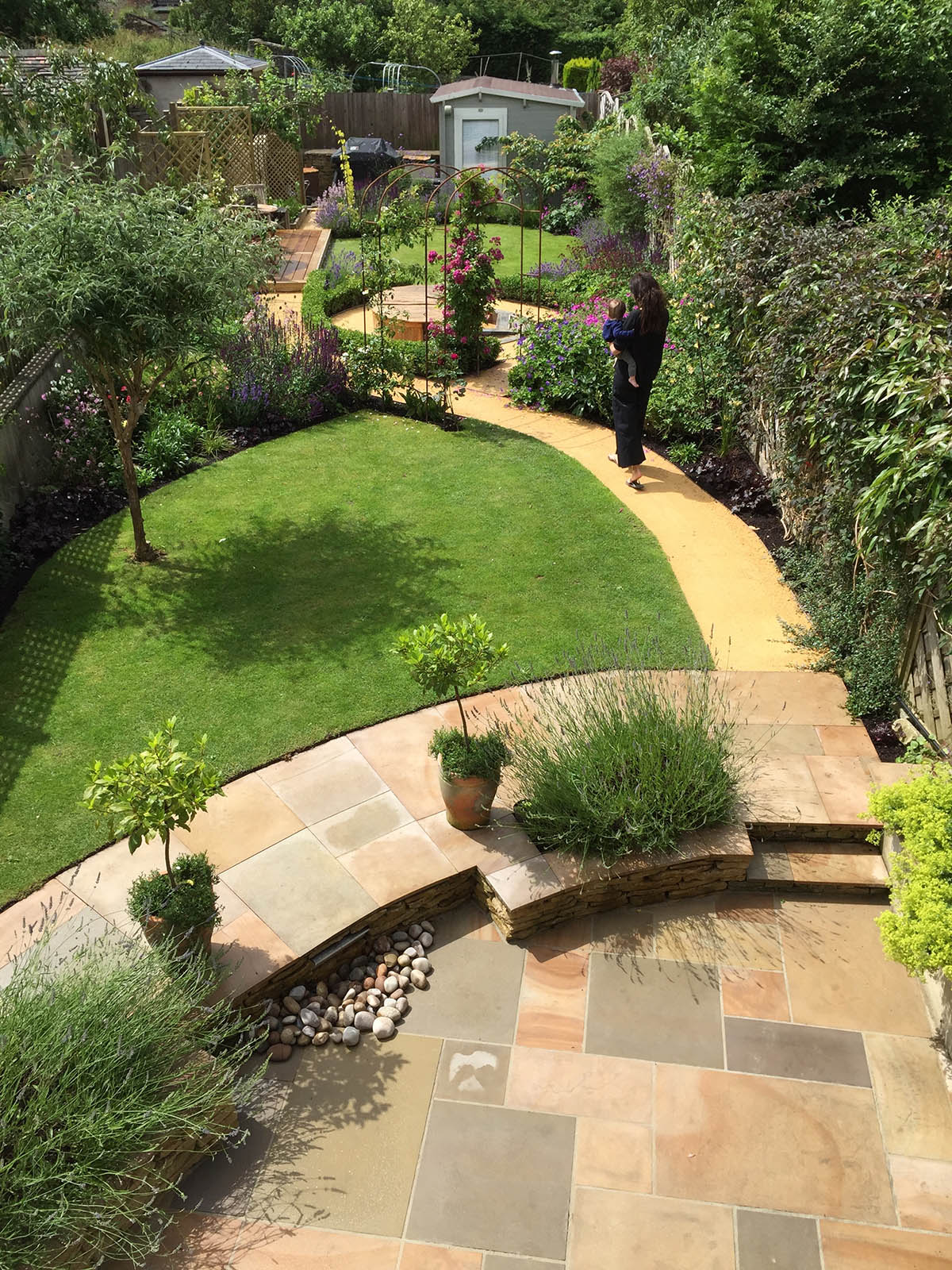 Natural stone paving terrace with a child friendly  water feature  edged with english lavender