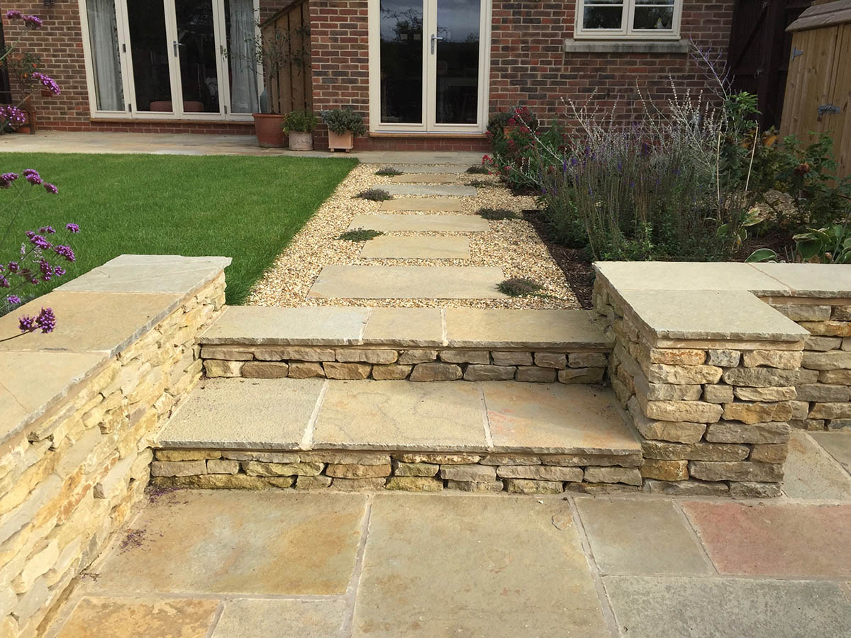 Natural stone paving terrace with Cotswold stone steps leading to a gravel path with stepping stones