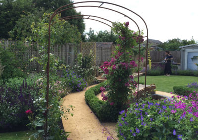 Metal rose arch over a self-bind gravel path
