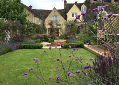 The family garden with entertaining lawn, wooden decking and rose arches