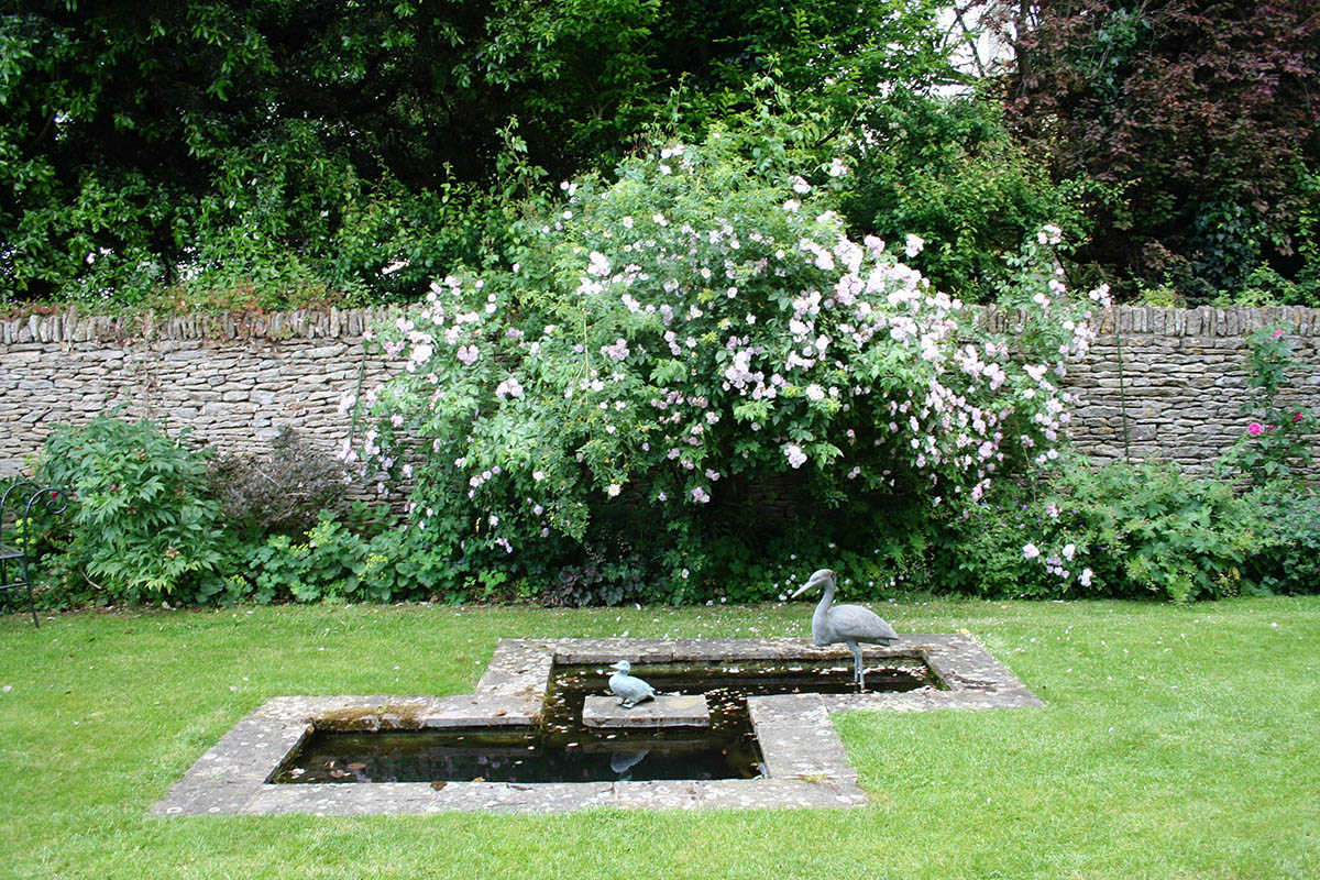 A simple elegant small pond edged with Forest of Dean stone