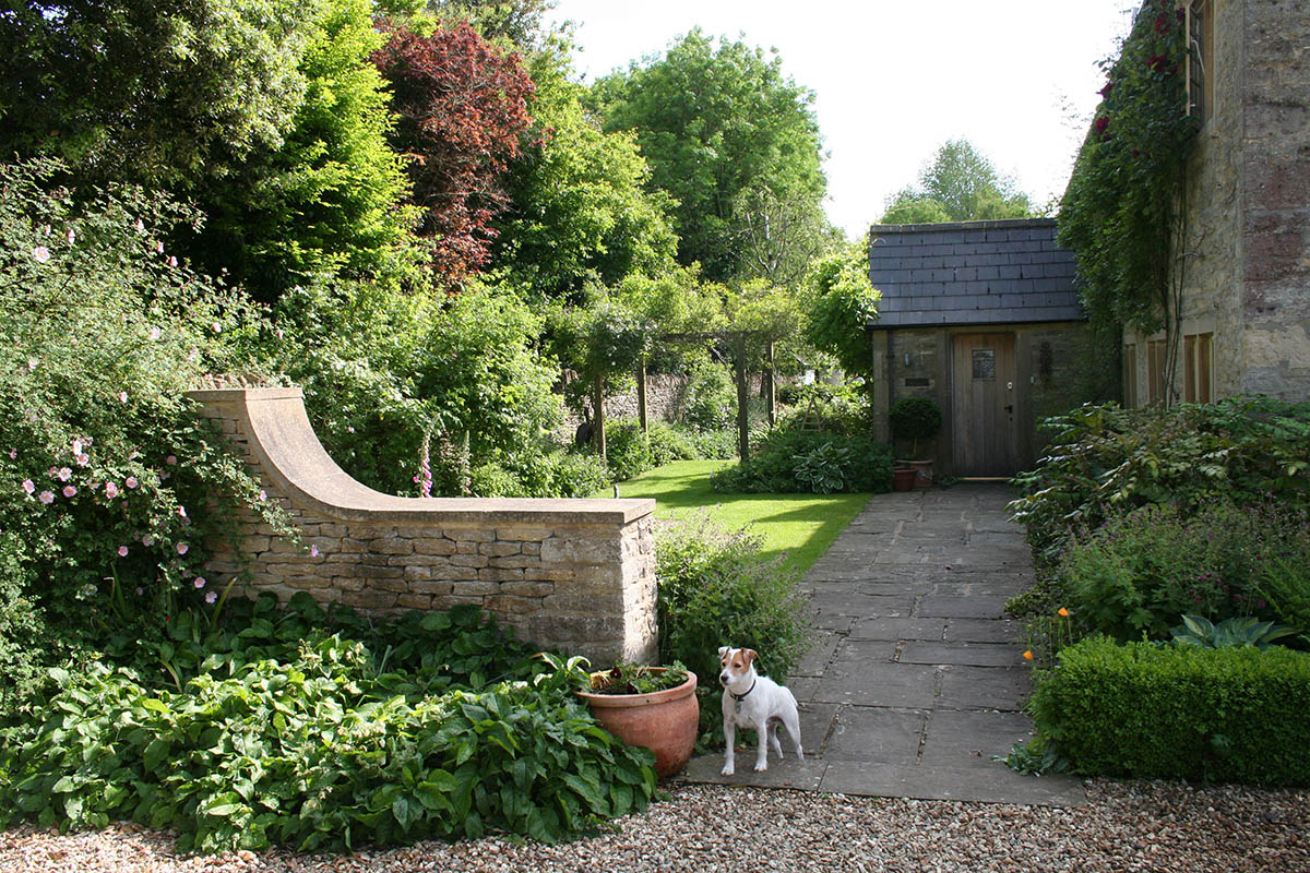 The curved Cotswold stone wall welcomes people into the garden