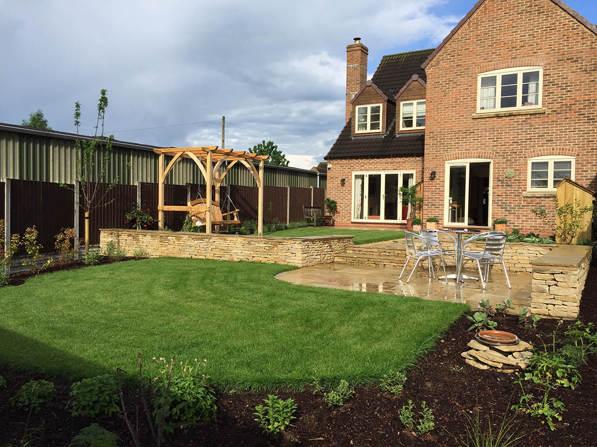 Family garden with an entertaining area of natural stone paving edged with Cotswold stone walls and natural stone paving used for the coping stones