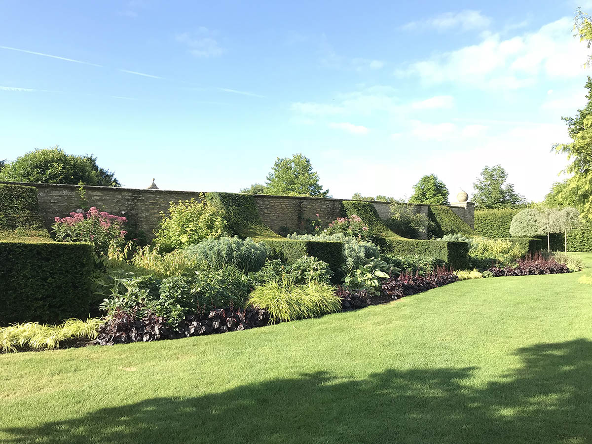 A large herbaceous border with repeat planting divided by Yew buttresses