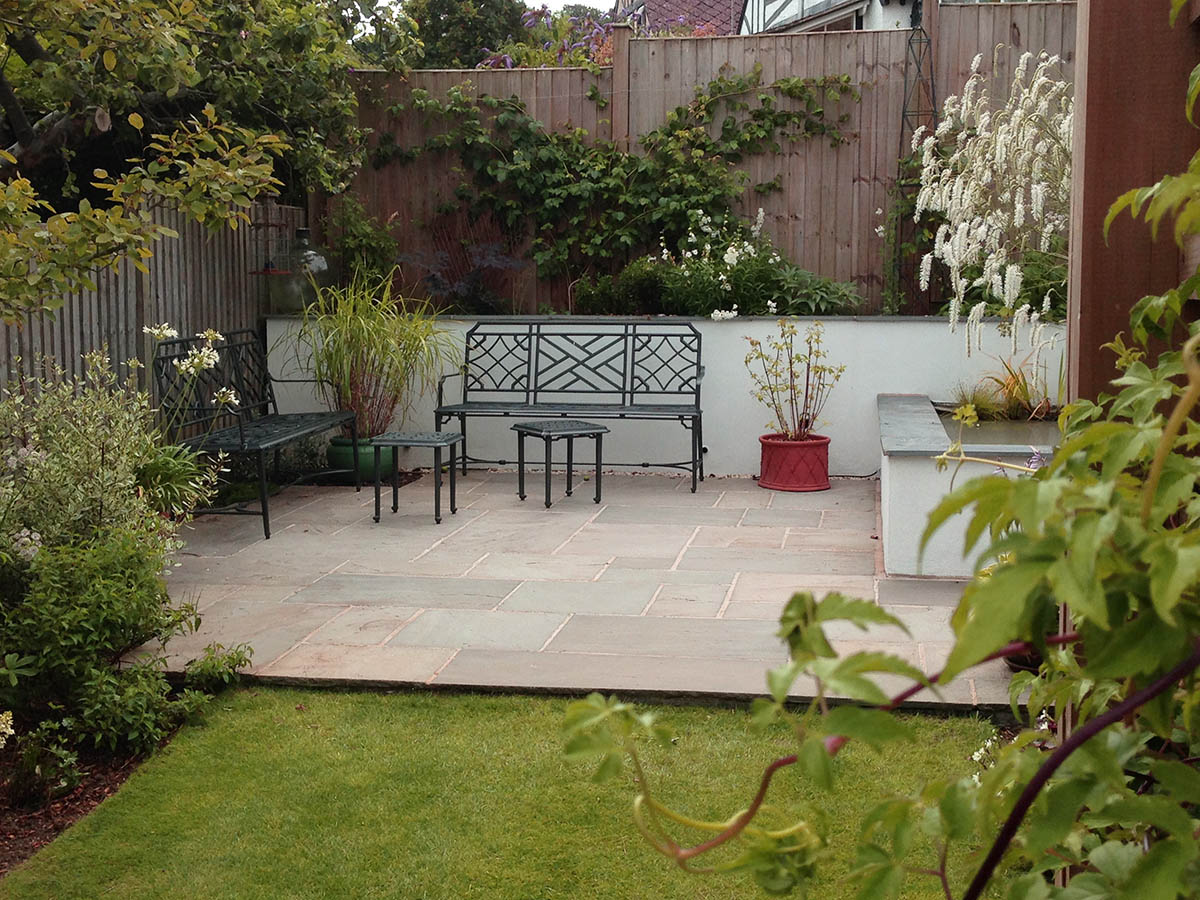 Natural stone paving seating area beside a rendered contemporary water feature with slate coping